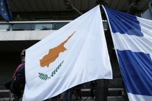 A protester holds a Cypriot flag during a rally against a levy on bank deposits in Cyprus, outside of the European Union office in Athens